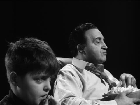 vidéos et rushes de b/w 1961 side view man + son watching tv + eating / documentary - reportage