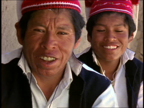 stockvideo's en b-roll-footage met portrait man + son with red caps + black vests smiling / isla taquile, lake titicaca - peruaanse etniciteit