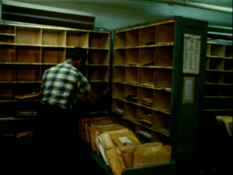 man sorting mail into boxes in mail room letters being placed into cubby bin / post office employees placing mail bags packages onto conveyor behind... - organisieren stock-videos und b-roll-filmmaterial