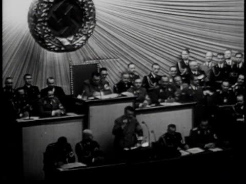 vídeos y material grabado en eventos de stock de man speaking at podium / crowd listening / man speaking at podium / crowd cheering - 1939