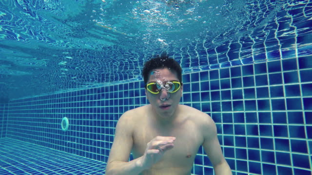 man speaking, greeting, gesturing underwater in swimming pool - swimming goggles stock videos & royalty-free footage