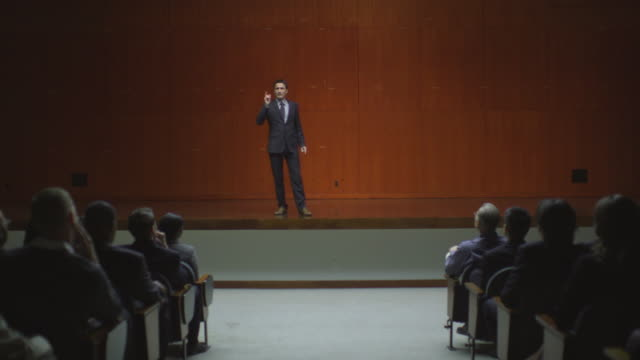 ws ds man speaking on stage to audience / south orange, new jersey, usa - applaudieren stock-videos und b-roll-filmmaterial