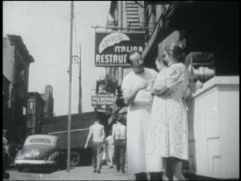 b/w 1949 man speaking with woman holding baby on sidewalk in little italy / nyc - 1949 bildbanksvideor och videomaterial från bakom kulisserna