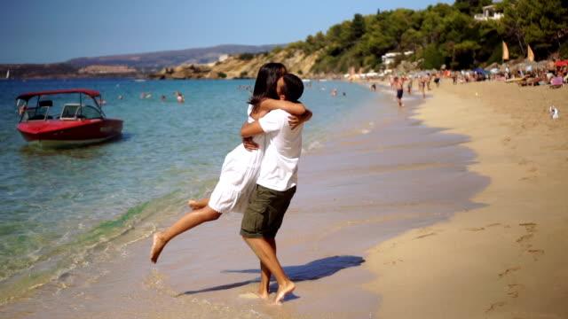 der mann drehte sich um seine freundin am strand. - griechenland stock-videos und b-roll-filmmaterial