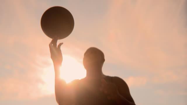 LA CU SHAKY Man spinning basketball on finger on outdoor court, Jacksonville, Florida, USA