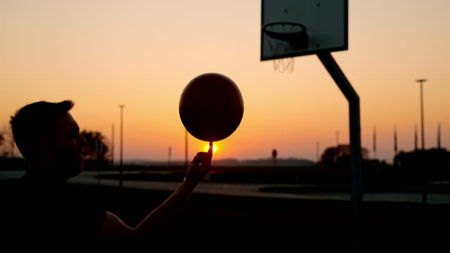 ms super slow motion man spinning basketball on outdoor basketball court at sunset - balance stock videos & royalty-free footage
