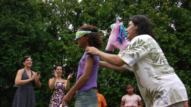 vídeos y material grabado en eventos de stock de man spinning blindfolded girl around who holds stick underneath pinata as people watch and clap in background / new jersey - palo parte de planta