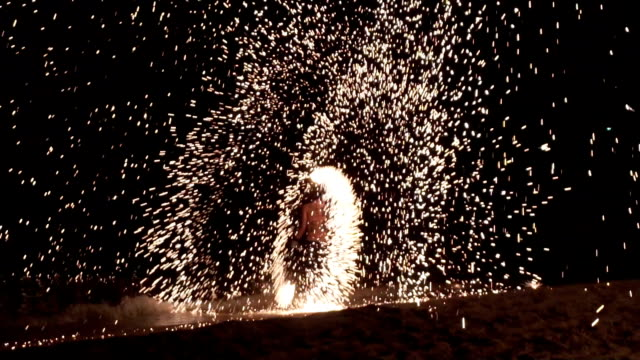 A Man Spinning Igniting Wire Wool Fire show, Amazing Firework nightlife show on beach