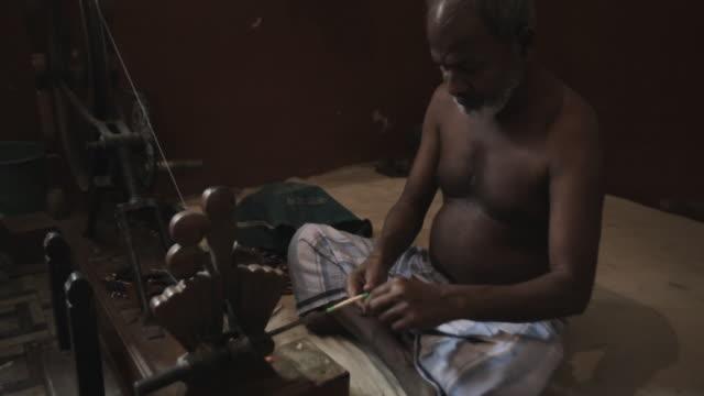 ws man spinning thread on spinning wheel / india - endast en medelålders man bildbanksvideor och videomaterial från bakom kulisserna