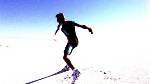 OVEREXPOSED SELECTIVE FOCUS man spinning + throwing discus in desert / White Sands, New Mexico