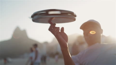 cu a man spins a tambourine on his finger on ipanema beach / rio de janeiro, brazil - rio de janeiro bildbanksvideor och videomaterial från bakom kulisserna