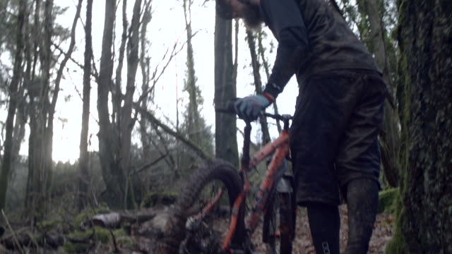 A man spitting while mountain biking in the woods.