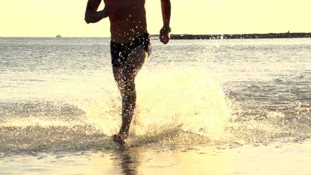 hd super slow mo: man splashing in shallow water - miami beach stock videos & royalty-free footage