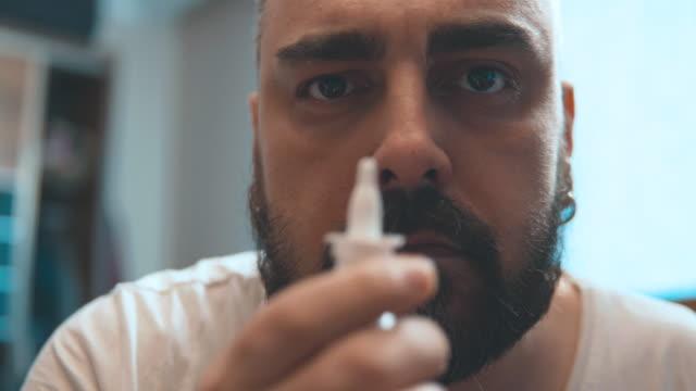 mann spritzt kleine dosis nasenspray in der nase. saisonale erkältung und grippe, allergie oder asthma. nasentropfen. - sprühen stock-videos und b-roll-filmmaterial