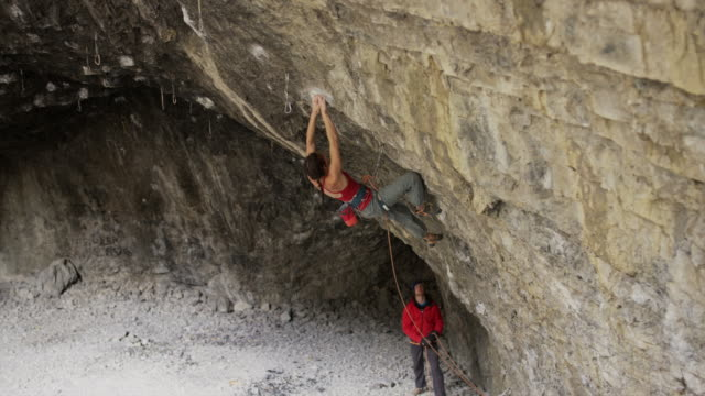 man spotting for woman rock climbing in cave / american fork canyon, utah, united states - american fork canyon stock videos and b-roll footage