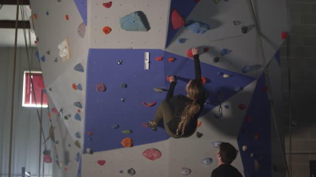 man spotting woman as she climbs up rock wall in gym - arrampicata libera video stock e b–roll