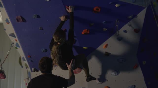 man spotting woman as she free climbs up wall - arrampicata libera video stock e b–roll