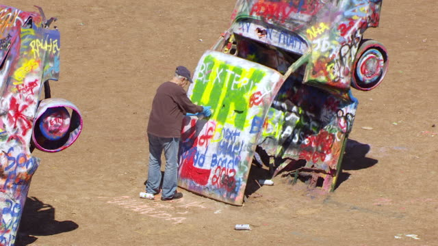 cu aerial ts zo man spray painting cadillac ranch in panhandle plains / texas, united states - zoom out stock videos & royalty-free footage
