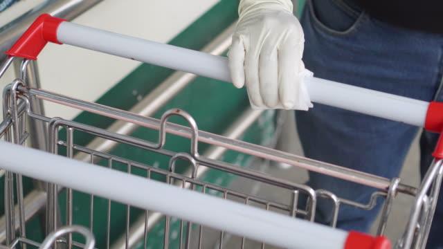 vídeos de stock e filmes b-roll de man spraying alchohol and rub shopping cart handle - luva peça de roupa