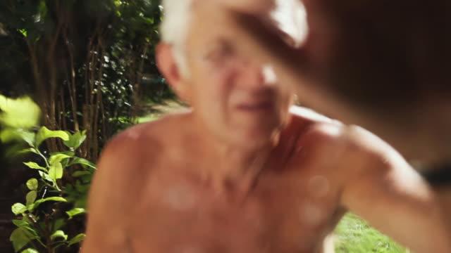 stockvideo's en b-roll-footage met cu man spraying garden and approaching glass / corsept, loire-atlantique, france - alleen één seniore man