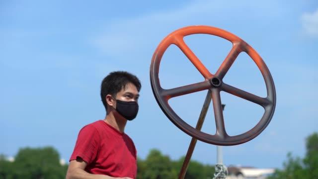 自転車の車輪にペンキを吹き付ける男。 - カスタマイズ点の映像素材/bロール