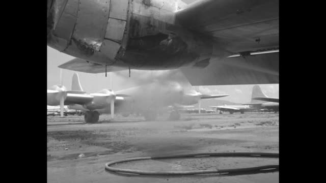 man spraying plane propeller engine to wash away protective coating / propeller area being sprayed, planes in bg / travel shots rows of b-29s parked... - b29 stock videos & royalty-free footage