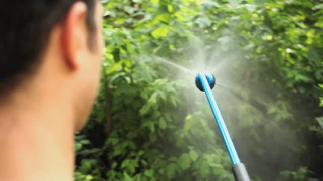 vídeos y material grabado en eventos de stock de cu r/f man spraying plants in backyard with sprinkler / jersey city, new jersey, usa - jardin