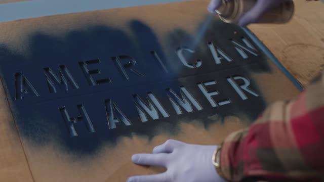 vidéos et rushes de cu man sprays cardboard stencil that spells out 'american hammer' with dark colored spray paint - vêtement de peau