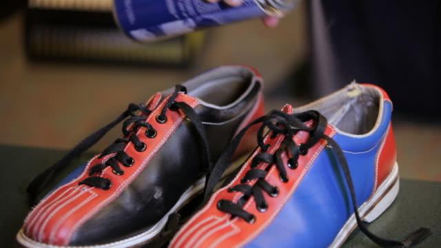 vídeos de stock, filmes e b-roll de man sprays deodorant in bowling shoes - sapato de boliche