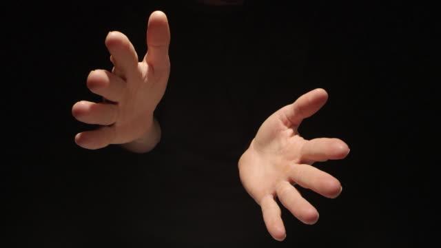 vídeos y material grabado en eventos de stock de hombre que se separa de las manos sobre fondo negro - golpear