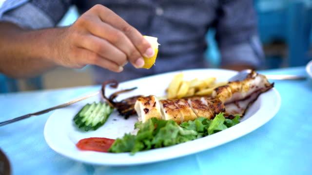 man squeezes lemon into squid - mediterranean culture stock videos & royalty-free footage
