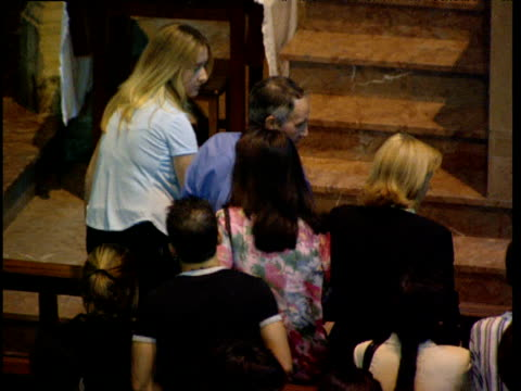 stockvideo's en b-roll-footage met man squeezes past members of congregation to kneel on pew in catholic church basque country spain - gelovige