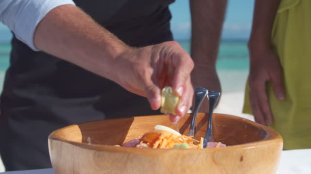 a man squeezing lemon on a poke salad lunch in a bowl. - territori francesi d'oltremare video stock e b–roll