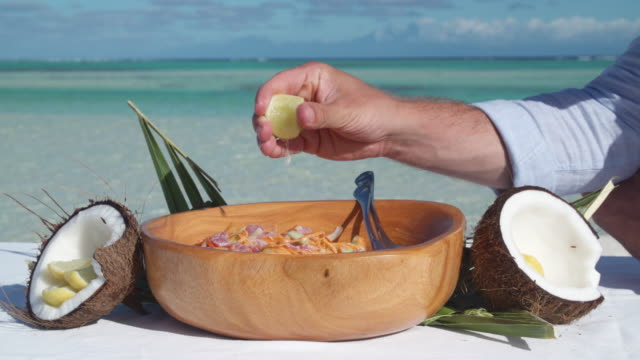 vídeos de stock, filmes e b-roll de a man squeezing lemon on a poke salad lunch in a bowl. - frutos do mar