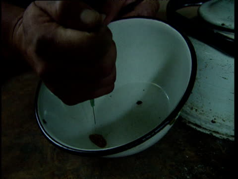 vídeos de stock, filmes e b-roll de man squirts liquid from hypodermic syringe over opium in enamel bowl during preparation tajikistan - abuso de substâncias