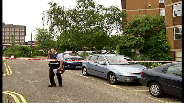 man stabbed to death at his home in northwest london england london hendon verulam court ext police officer standing next police cordon tape in area... - northwest england stock videos and b-roll footage