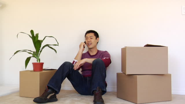 vídeos de stock e filmes b-roll de ws man stacking boxes, then sitting down against wall and talking on cell phone in new house / los angeles, california, usa - sentar se