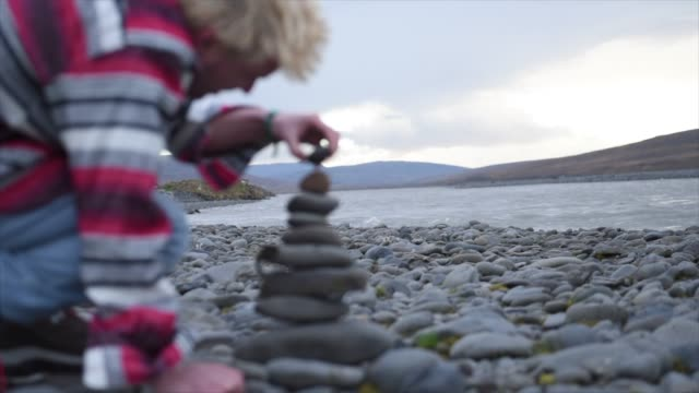 vídeos y material grabado en eventos de stock de a man stacking rocks to make a cairn in iceland, europe. - montón de piedras