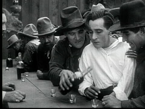 1916 b/w montage cu ms man staggering into saloon, drinking with encouragement from other bar patrons, 1880s / santa monica, california, usa - trinken stock-videos und b-roll-filmmaterial