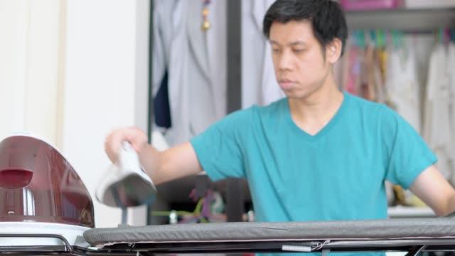 uomo in piedi e vestiti da stiro nel soggiorno - asse da stiro video stock e b–roll