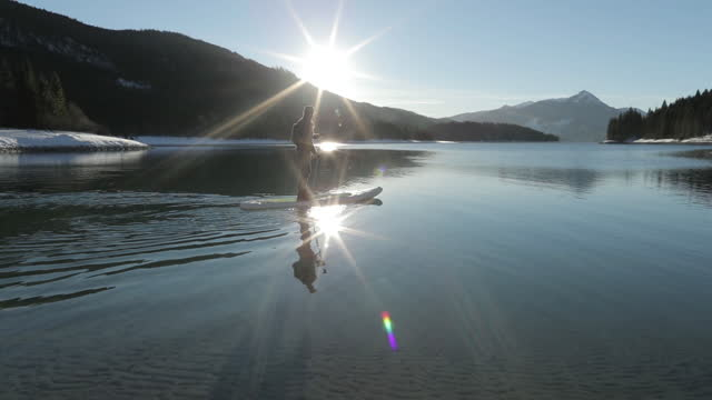 man stand up paddle surfing on a lake in winter - paddel stock-videos und b-roll-filmmaterial