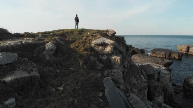 man standing alone on a rock in a coast - klippe stock-videos und b-roll-filmmaterial