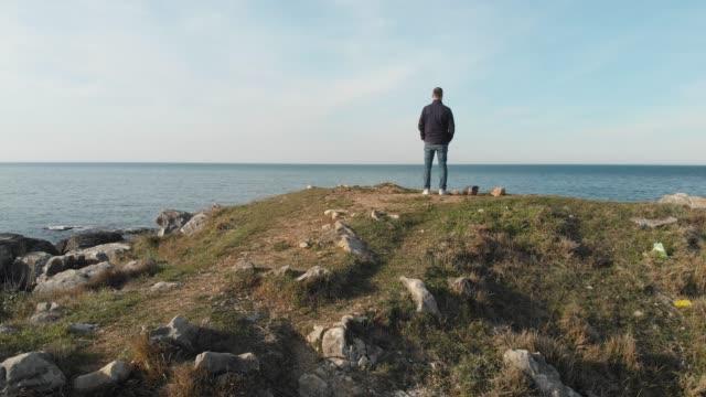 vídeos de stock, filmes e b-roll de homem que está sozinho em uma rocha em uma costa - horizonte