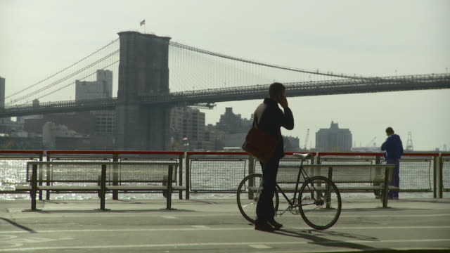 vídeos y material grabado en eventos de stock de ws man standing at bicycle on waterfront pathway and talking on mobile phone, brooklyn bridge and city skyline seen across east river / new york city, new york, usa - bolsa de hombro