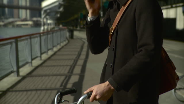 cu tu man standing at bike and talking on mobile phone on waterfront pathway / new york city, new york, usa - 30 34 jahre stock-videos und b-roll-filmmaterial