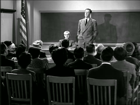 b/w 1946 man standing at front of classroom lecturing to adults seated in chairs - seminar stock videos & royalty-free footage