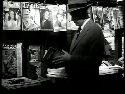 man standing at news stand thumbing through small book. article 'japan has already won her war' by clark lee. - rivista pubblicazione video stock e b–roll