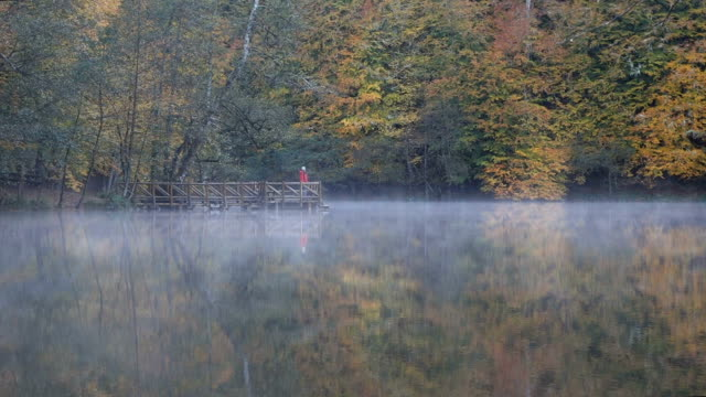 man standing at the pier on foggy lake