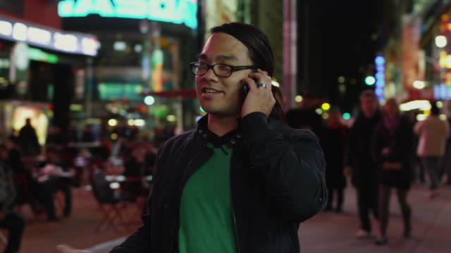 ds ms man standing at times square and talking on phone at night / new york city, new york state, usa - one night stand stock videos & royalty-free footage