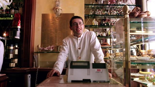 PAN PORTRAIT man standing behind cash register in bakery laughing + talking / Milan, Italy